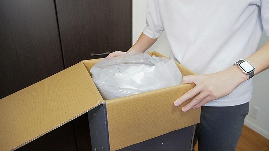 NELLマットレスが圧縮されてぐるぐるの状態でダンボールに詰められている画像。
